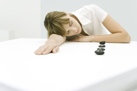 Woman resting head on table beside lined up stones