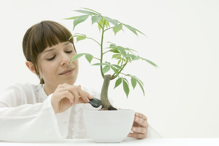Woman placing stones around base of potted plant LANG_EVOIMAGES