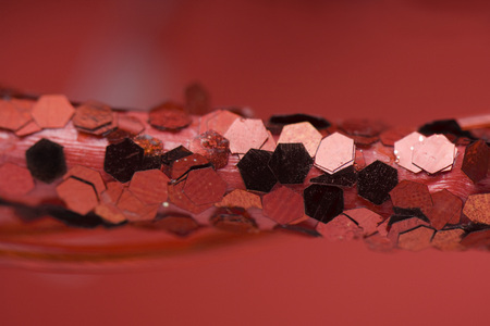 Christmas decoration covered in red sequins, extreme close-up LANG_EVOIMAGES
