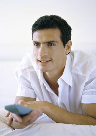 Man holding remote control LANG_EVOIMAGES