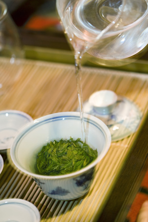 Hot water poured from glass teapot over tea leaves in gaiwan cup