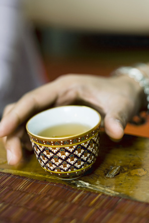 Hand reaching for colorful tea cup full of tea