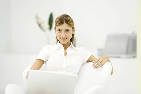 Woman sitting in armchair, holding laptop computer, smiling at camera LANG_EVOIMAGES