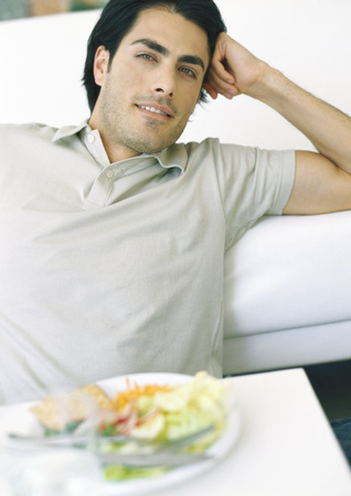 Man sitting at table, with meal, leaning back and looking away
