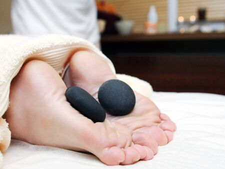 Getting a stone massage at spa, stones on foot photo