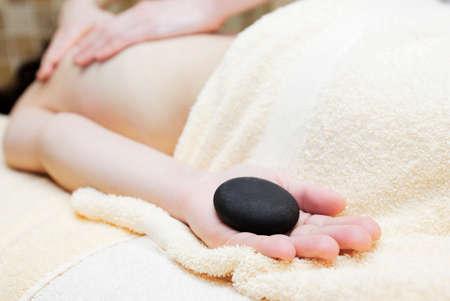 Getting a stone massage at spa photo