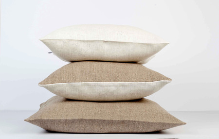White and natural linen pillows stack isolated. Pillows for farmhouse decor. Stock Photo