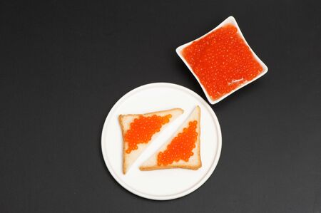Red caviar in a saucer on a black background Stockfoto