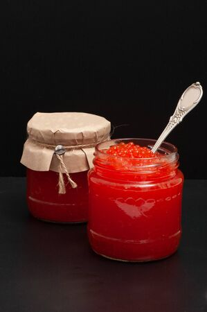 Red caviar in a jar on a black background