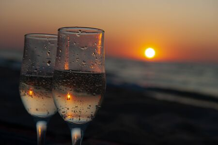 Glass of wine on sunrise, sunset background