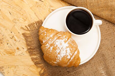 Croissant with a cup of coffee on a plate. Top view Foto de archivo - 132029844