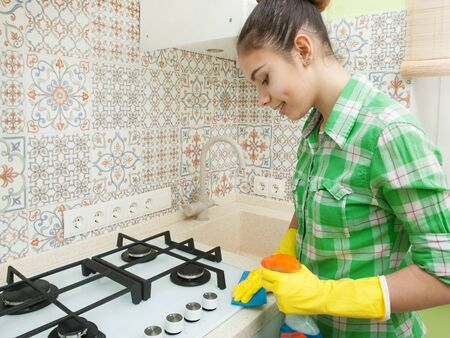 Girl Gloved washes cupboards, stove and sink in the kitchen 스톡 콘텐츠