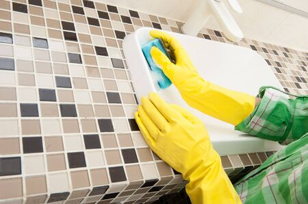 Gloved housewife washes a sink in the bathroom