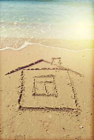 Drawing house in the sand on the seashore Stok Fotoğraf