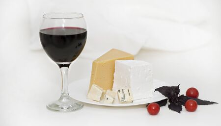 Glass with red wine and cheese on a plate on a light background Stok Fotoğraf