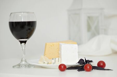 Glass of red wine and cheese on a plate