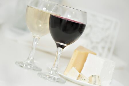 Glasses with red and white wine and cheese on a plate