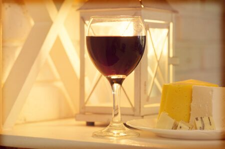 Shelf with a glass of wine and a plate of cheese