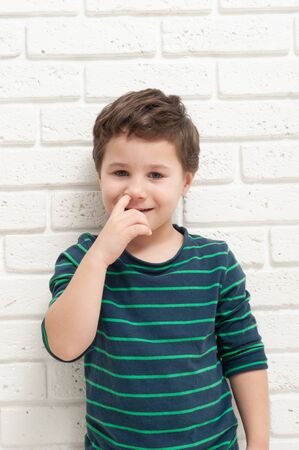 Little boy picks his nose with his finger