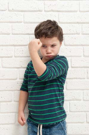 An angry frowning boy threatens with his fist Banque d'images