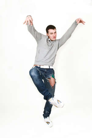 Young man dancing in a gray sweatshirt on a white background