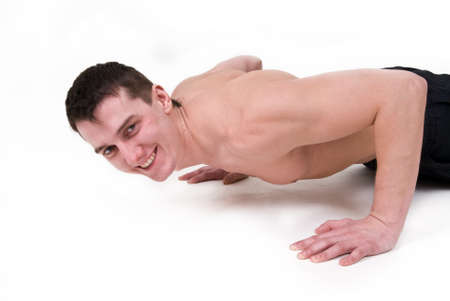 Man with a naked torso doing push-ups on a white background