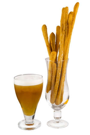 Grissini sticks and glass with beer on white background