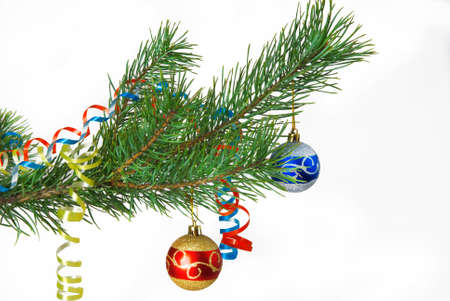 Christmas tree branch with Christmas decorations, tinsel and balls
