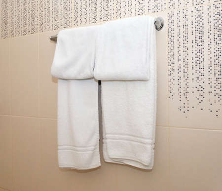 White towels hang on the wall with beige tiles Stock fotó