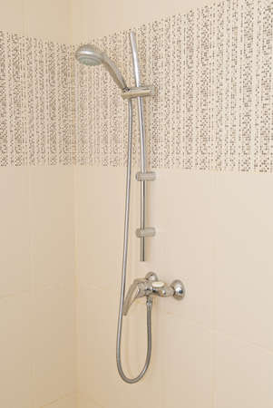 Shower hanging on the wall with beige tiles