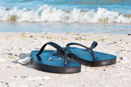 Black flip flops on the seashore