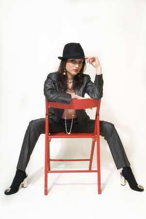 Young business woman in business clothes is sitting on a chair on a white background