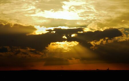 Yellow sky at sunset with orange sunrays