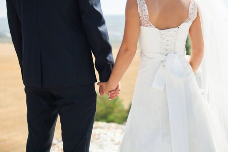 Bride and groom walking together holding their hands Foto de archivo
