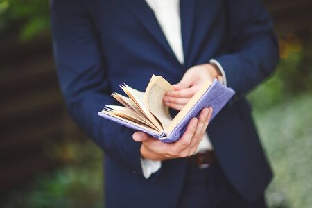 A man in a blue suit reads a book.