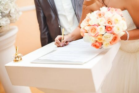 Bride and groom signing marriage wedding certificate at registry.