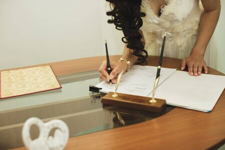 Bride and groom signing marriage wedding certificate at registry. Фото со стока