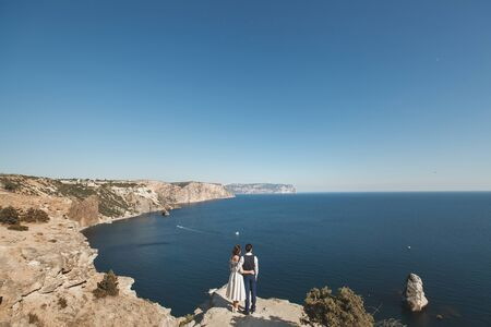 bride and groom on the precipice of the mountain. the ocean. sea