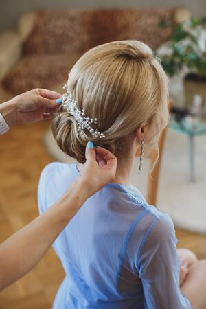 Hair stylist makes the bride a wedding hairstyle with fresh flowers. Banque d'images
