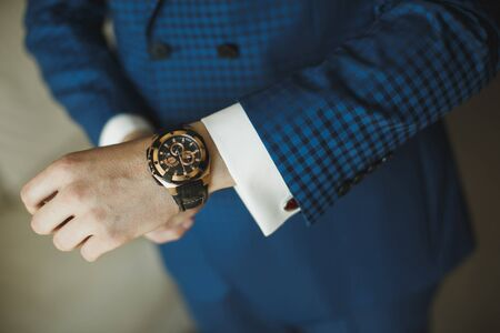 A businessman in a blue suit checks the time with his watch .