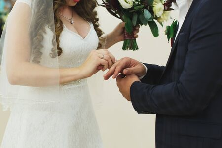 Newlyweds exchange rings, groom puts the ring on the brides hand in marriage registry office