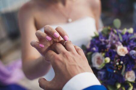 la novia y el novio ponen en el dedo un anillo de bodas.