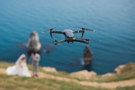 ドローンは、海の近くの崖の上に新郎新婦を撮影します。