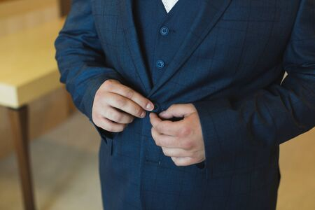 Close-up view of the hands of the groom buttoning the wedding jacket