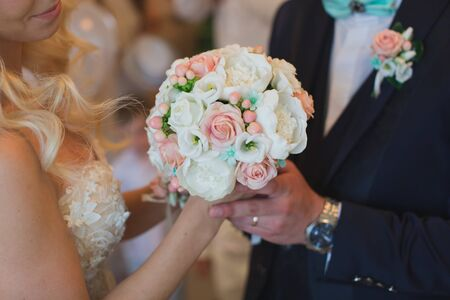 Groom in a suit gives the bride a white and peach wedding bouquet