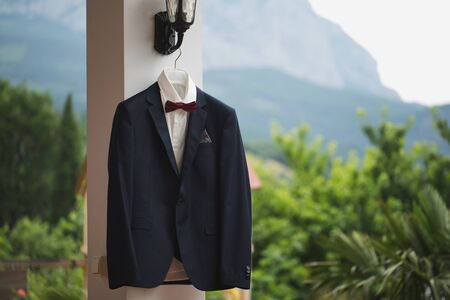 Groom suit jacket on a hanger mountain in the background.