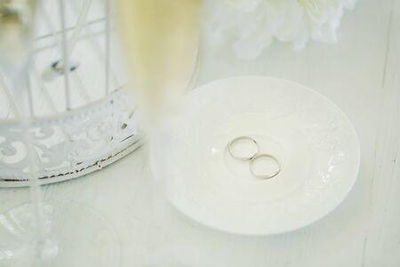 Wedding rings on a ceramic white saucer 免版税图像