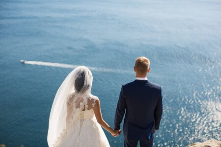 Bride and groom holding hands on a cliff against the sea