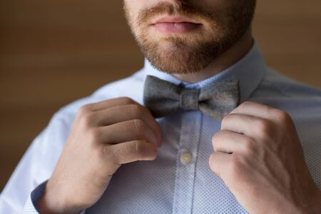 The groom puts on a bow tie in the morning at the window Foto de archivo