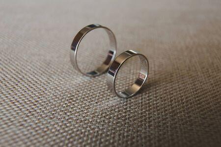 beautiful silver wedding rings lying on grey fabric